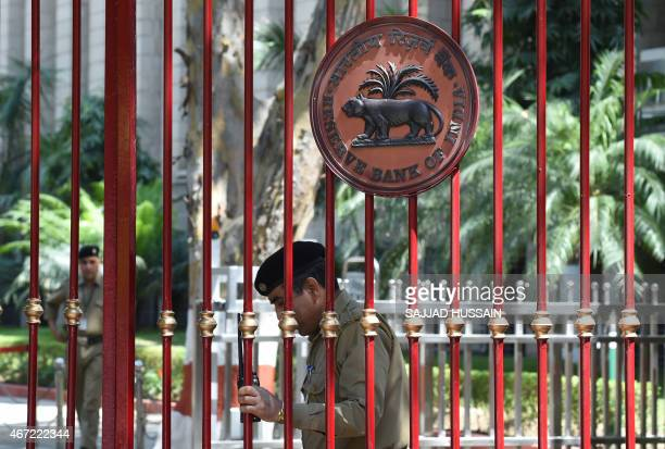 An Indian security guard closes the main gate of the Reserve Bank of India office during a meeting by Indian finance minister Arun Jaitley with the...
