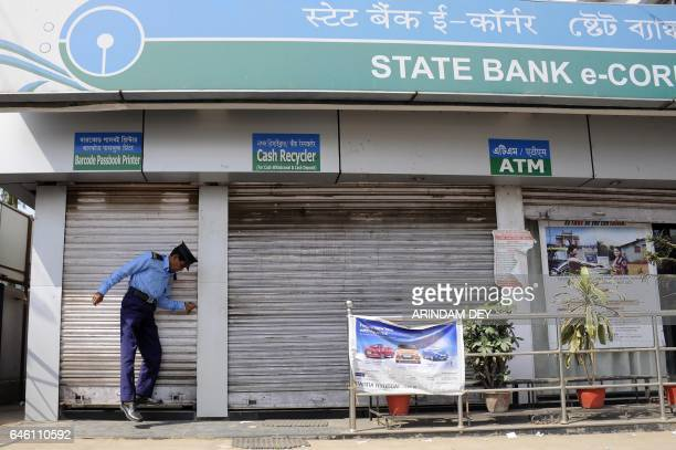 An Indian security guard pulls down the shutters of a state bank's ATM branch during a nationwide bank strike in Agartala the capital of the...
