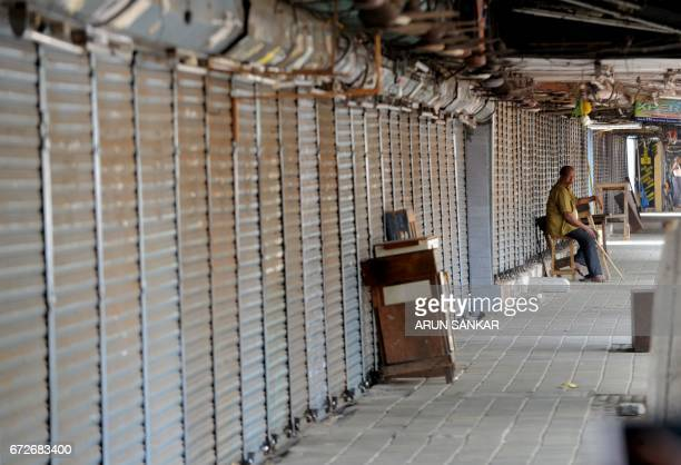 An Indian security guard sits next to shuttered stores during a statewide strike in support of farmers in Chennai on April 25 2017 Tamil Nadu state...