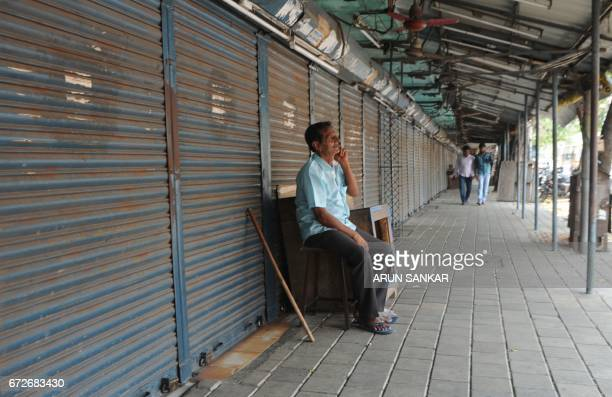 An Indian security guard speaks on his phone next to shuttered stores during a statewide strike in support of farmers in Chennai on April 25 2017...