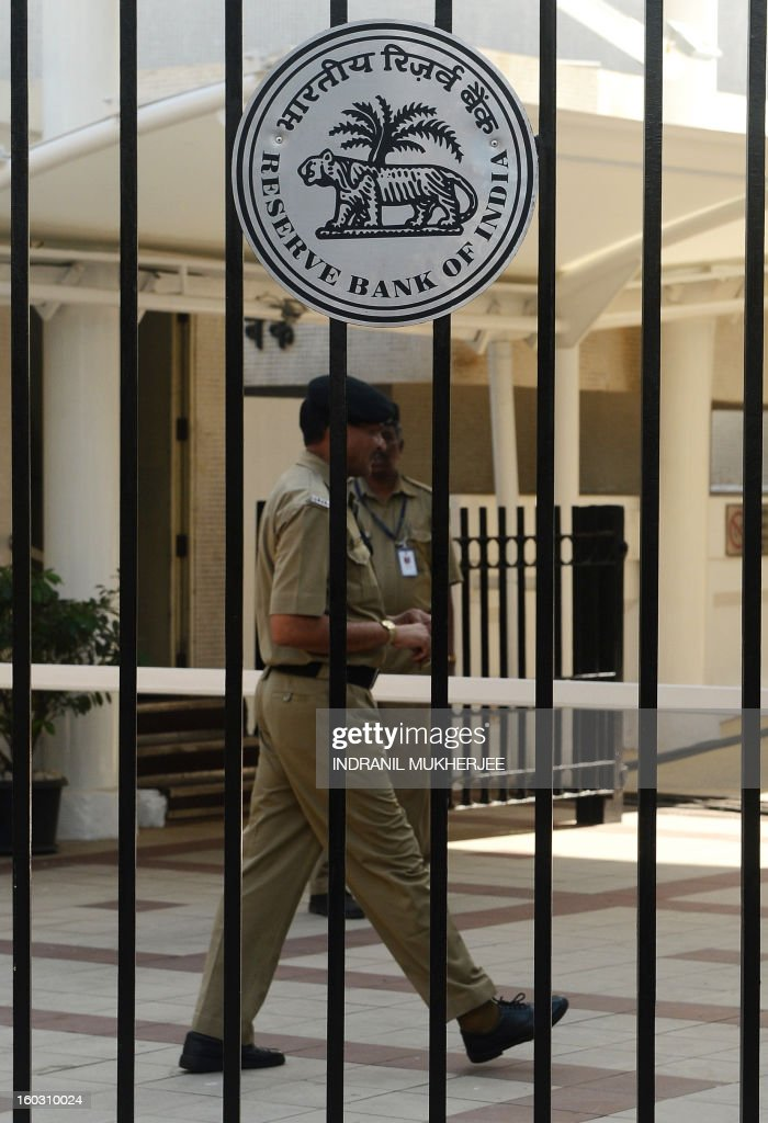 An Indian security officer walks past the main entrance of the Reserve Bank of India (RBI) headquarters in Mumbai on January 29, 2013. India's central bank cut its main interest rates by 25 basis points, in its first reduction for nine months as it seeks to kick start the slowing economy.