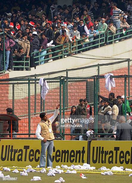 An Indian security official gestures to supporters as they throw debris onto the pitch after the cancellation of the fifth and final One Day...