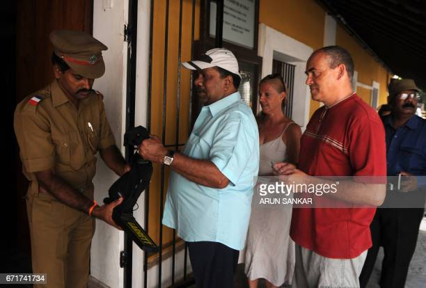 An Indian security official inspects a bag of a IndoFrench citizen as he arrives to cast his vote at a polling booth in Puducherry on April 23 before...