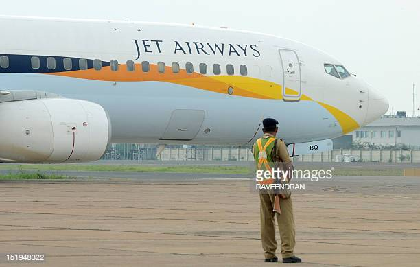 An Indian security official looks on as an aircraft of Jet Airways taxies after landing at Indira Gandhi International Airport in New Delhi on...
