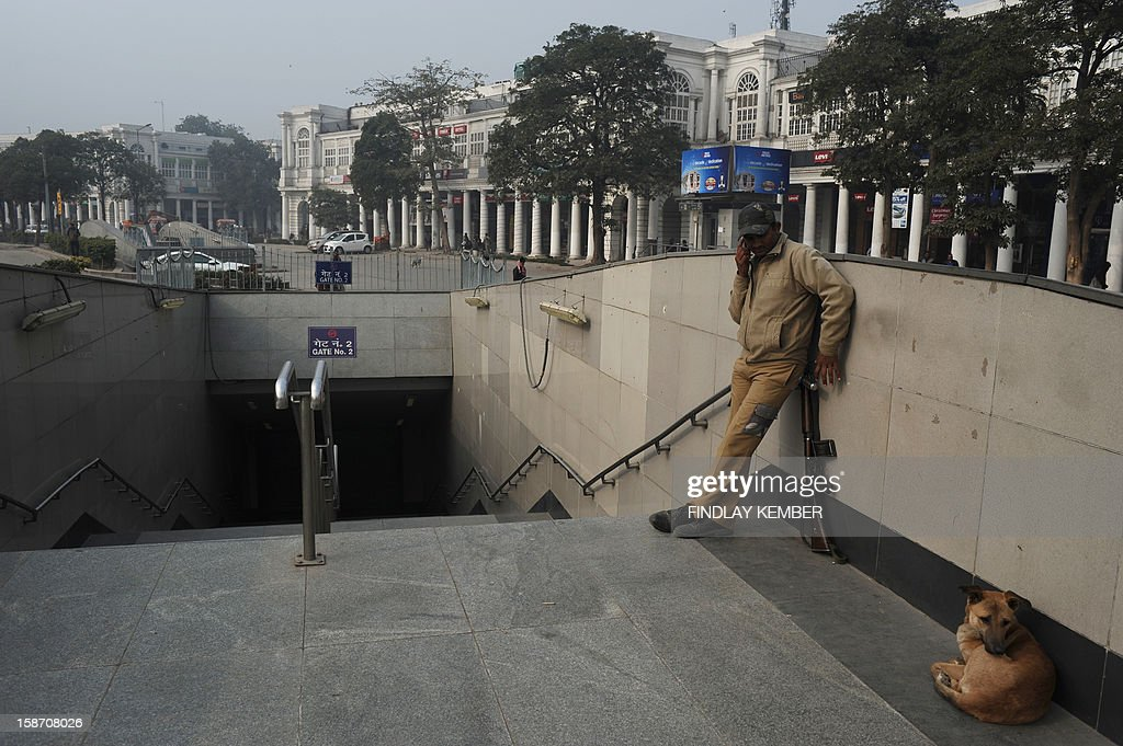An Indian security official speaks on his cellular telephone at a closed entrance to The Delhi Metro in Connaught Place in New Delhi on December 25, 2012. An Indian policeman injured in clashes during a protest over a gang-rape in New Delhi has died, a police spokesman said, as much of the city centre remains sealed off following the violence. Police barricaded roads leading to India Gate, an imposing war memorial in the centre of the city, that has become a hub of the protests by mostly college students. Many metro rail stations in fog-shrouded Delhi were also closed. AFP PHOTO/Findlay KEMBER
