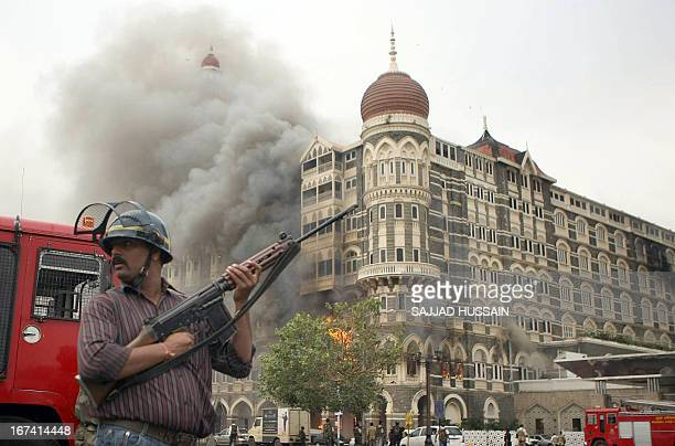 An Indian security official stands alert as smoke and flames billow out from a section of The Taj Mahal hotel in Mumbai on November 29 2008 Indian...