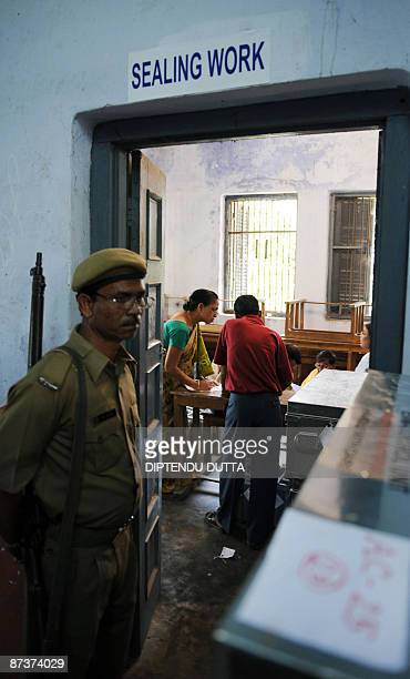 An Indian security official stands guard as a polling officer of the Election Commission of India counts votes in an Electronic Voting Machine during...