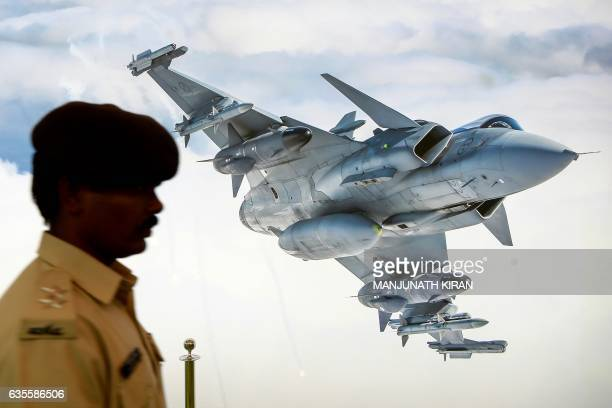 An Indian security official walks past a poster of a fighter aircraft at an aviation stall in the exhibition area on the third day of the 11th...