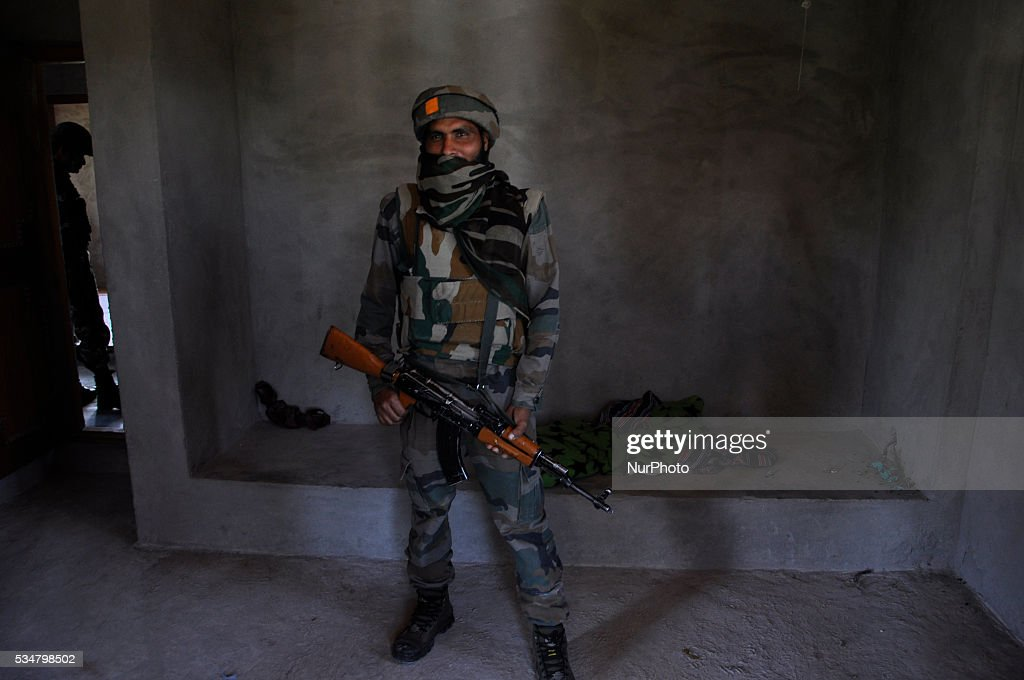 An indian security personal stands guard in a near by house next to the gunbattle site in Khonshipora 25 miles west of srinagar on May 27,2016.Two rebels were killed by indian forces during a brief gunfight.