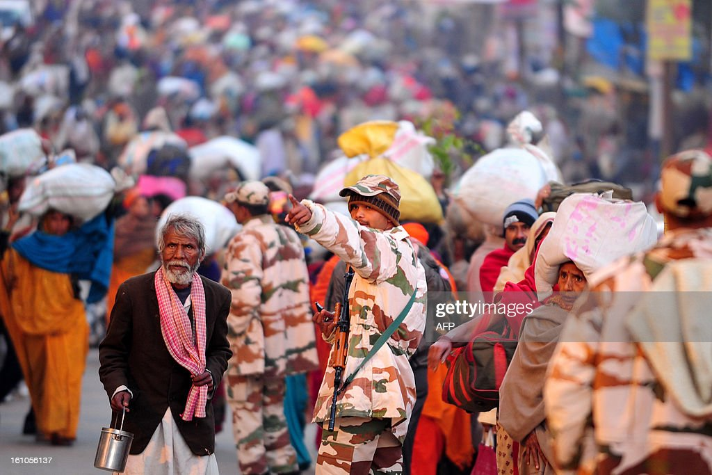 An Indian security personnel gives directions to a devotee while others gather at Sangam or the confluence of the Yamuna, Ganges and mythical Sarawati rivers at sunrise during the Maha Kumbh festival in Allahabad on February 9, 2013. The Kumbh Mela in the town of Allahabad will see up to 100 million worshippers gather over 55 days to take a ritual bath in the holy waters, believed to cleanse sins and bestow blessings. AFP PHOTO/SANJAY KANOJIA