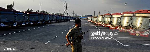 An Indian security personnel stand guards at the depot for Delhi Transport Corporation buses which will be used during the Commonwealth Games in New...