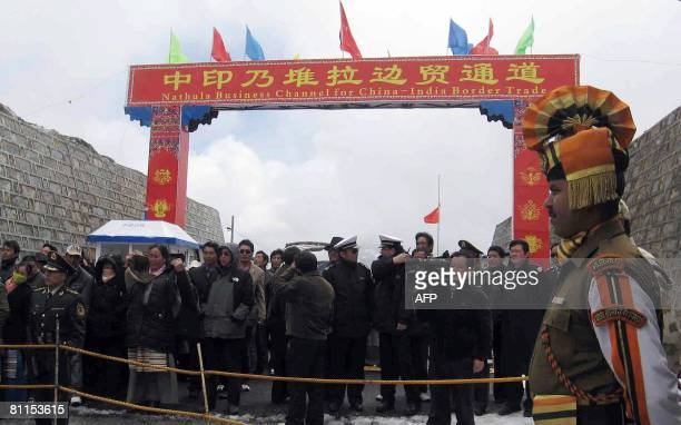 An Indian security personnel stands guard as Chinese traders wait to enter Indian territory after crossing the ChinaIndia border at the 15 000feet...