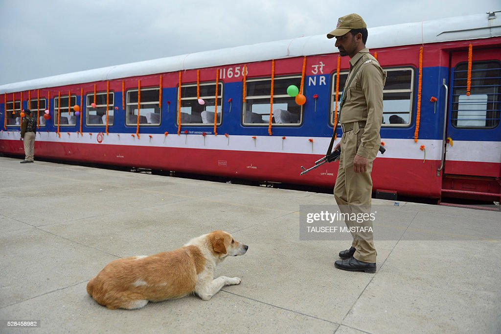 An Indian security personnel stands guard near a train during the launch a new train service in Anantnag on May 5,2016. Indian Railways has launched two new trains connecting the Kashmir Valley with the rest of the country in a project expected to be completed by 2020. / AFP / TAUSEEF