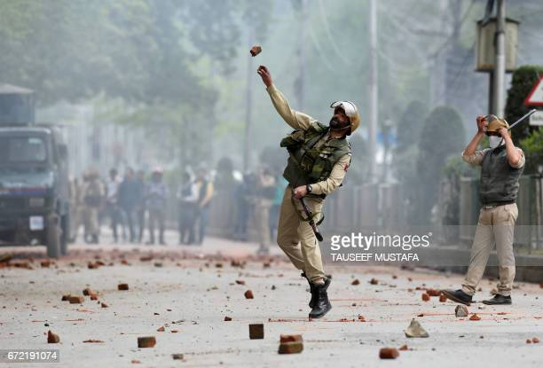An Indian security personnel throws a stone during clashes with Kashmiri students in central Srinagar's Lal Chowk on April 24 2017 Police fired into...