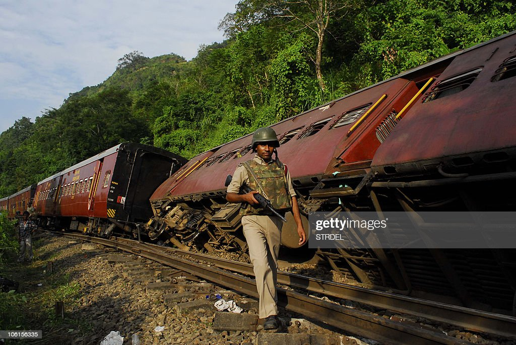 An Indian security serviceman walks past derailed compartments of the Barak Valley Express train, caused by a blast by suspected militants, near Halflong Railway Station, some 310 kms from Guwahati on October 27, 2010. Ten people were injured in the incident.