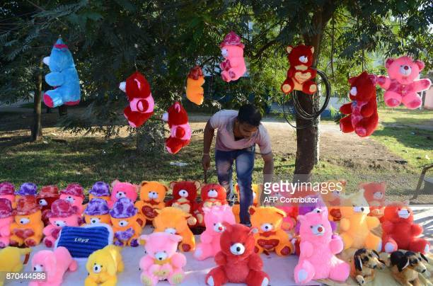 An Indian seller Nabin Kumar from Uttar Pradesh sells staff toys at his temporary road side stall in Bagdogra on the outskirts of Siliguri on...