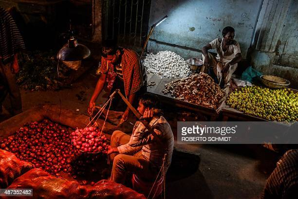 An Indian seller weighs a measure of onions on a handheld scale at a local market in south New Delhi on September 9 2015 The cost of India's staple...