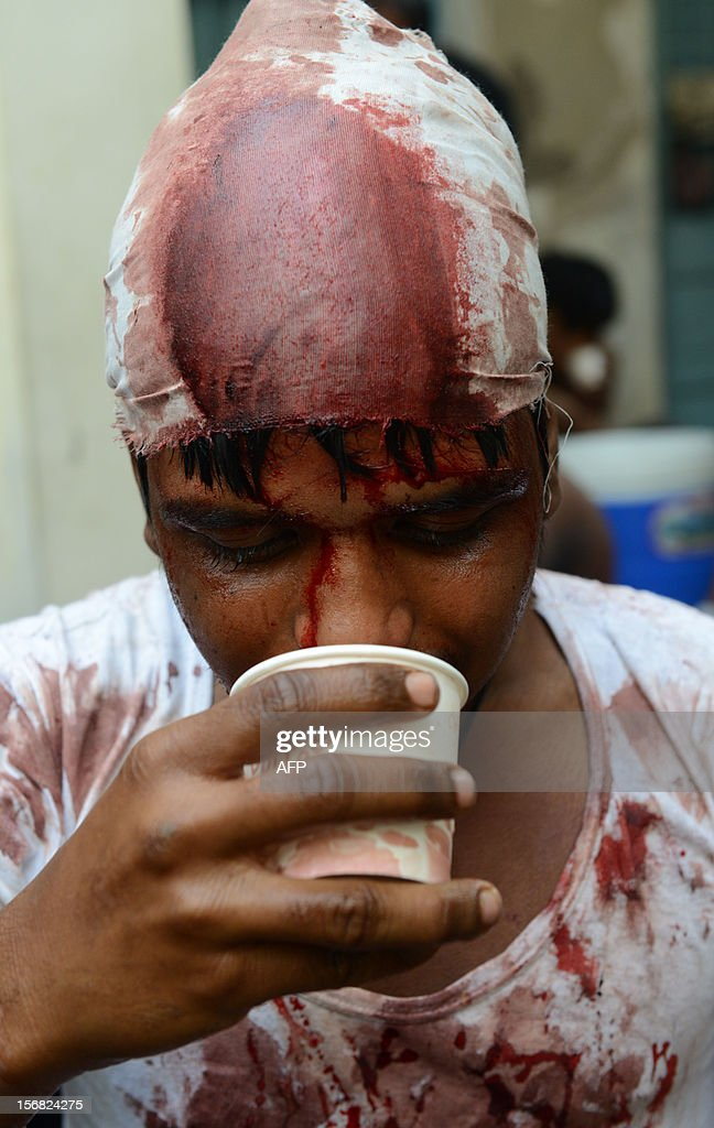 An Indian Shiite Muslim devotee sips a cup of coffee after performing ritual acts of self flagelation with a cluster of knives and chains during a religious procession in Ahmedabad on November 22, 2012. Rituals are held on the seventh day of Moharram, which commemorates the seventh century slaying of the Prophet Mohammed's grandson in southern Iraq. During the holy month of Muharram, large processions are formed and the devotees parade the streets holding banners and carrying models of the mausoleum of Hazrat Imam Hussain and his people, who fell at Karbala. Muslims show their grief and sorrow by inflicting wounds on their own bodies with sharp metal tied to chain with which they scourge themselves, in order to depict the sufferings of the martyrs AFP PHOTO / Sam PANTHAKY