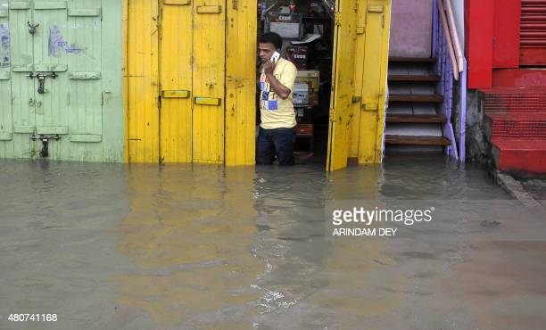 An Indian shop owner looks out of his store on a flooded street after heavy monsoon rain in Agartala on July 15 2015 AFP PHOTO/ ARINDAM DEY