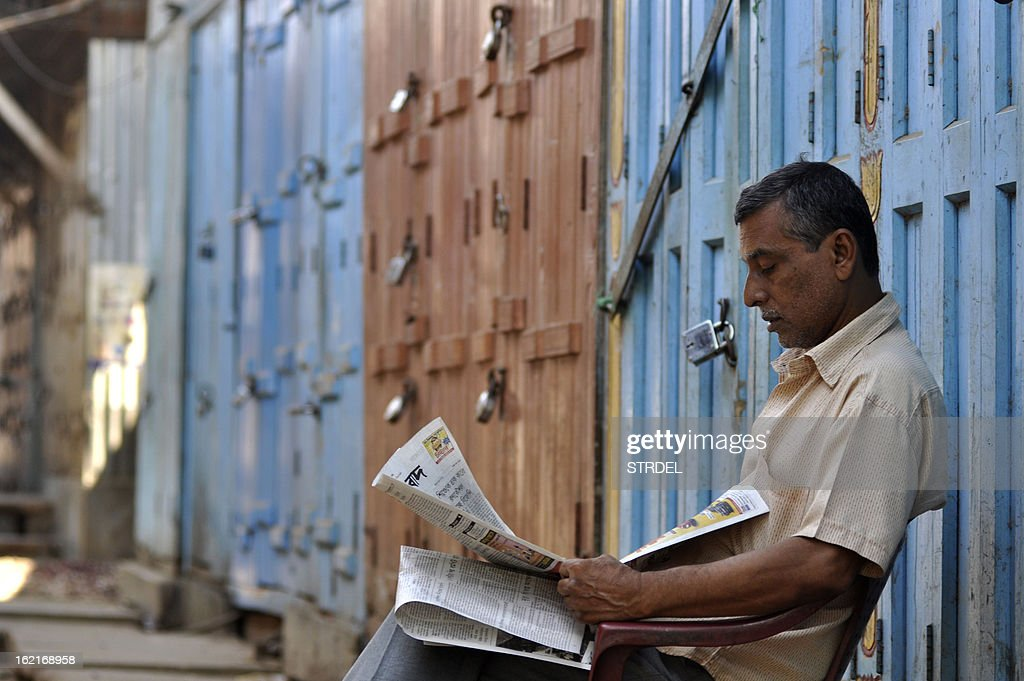 An Indian shop owner reads a newspaper inside of a closed wholesale market during a two day strike called by trade unions opposing the current UPA government's economic policies in Agartala,in the northeastern state of Tripur , on February 20, 2013. Millions of India's workers walked off their jobs in a two-day nationwide strike called by trade unions to protest at the 'anti-labour' policies of the embattled government. Financial services and transport were hit by the strike called by 11 major workers' groups to protest at a series of pro-market economic reforms announced by the government last year, as well as high inflation and rising fuel prices.