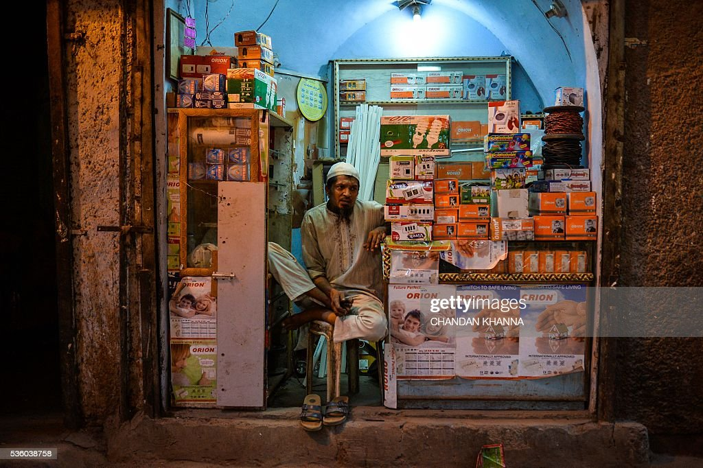 An Indian shop owner waits for customers in the old quarters of New Delhi on May 31, 2016. / AFP / CHANDAN
