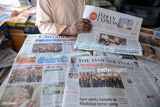 An Indian shop vendor displays newspapers featuring frontpage coverage of the Sunrisers Hyderabad team winning the trophy of 2016 Indian Premier...