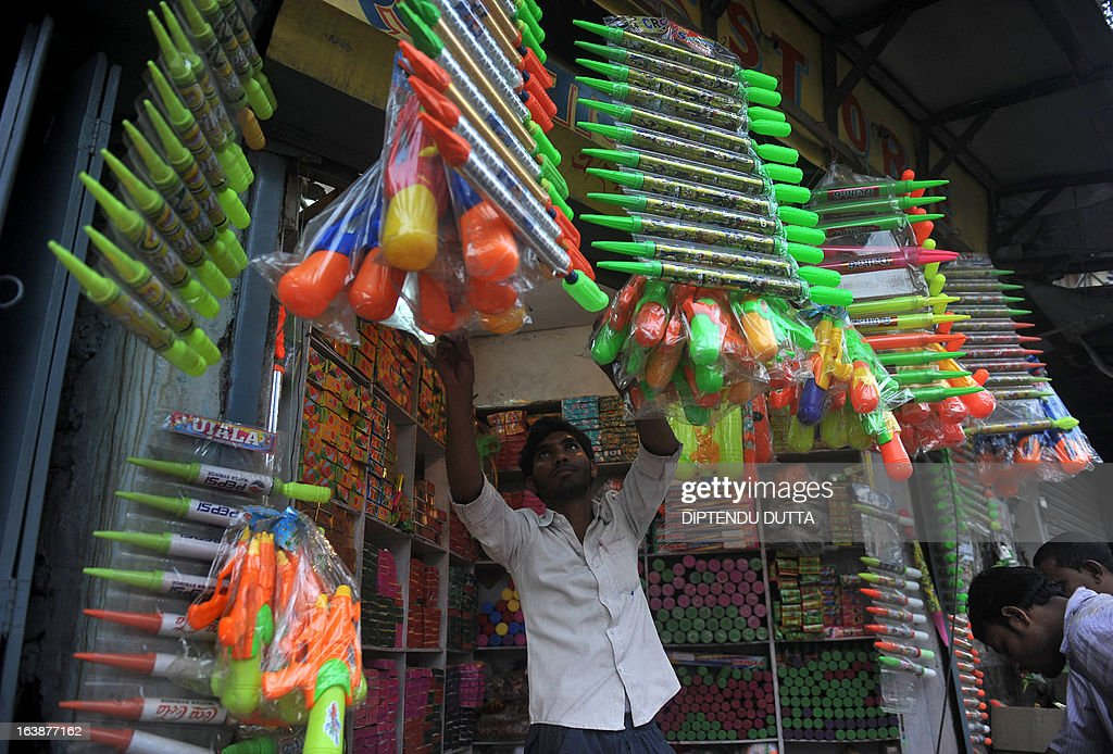 An Indian shopkeeper arranges water-guns used during celebrations of the Hindu festival, Holi in Siliguri on March 17, 2013. Holi, also called the Festival of Colours, is a popular Hindu spring festival observed in India at the end of the winter season on the last full moon day of the lunar month and falls on March 27 this year. AFP PHOTO/Diptendu DUTTA