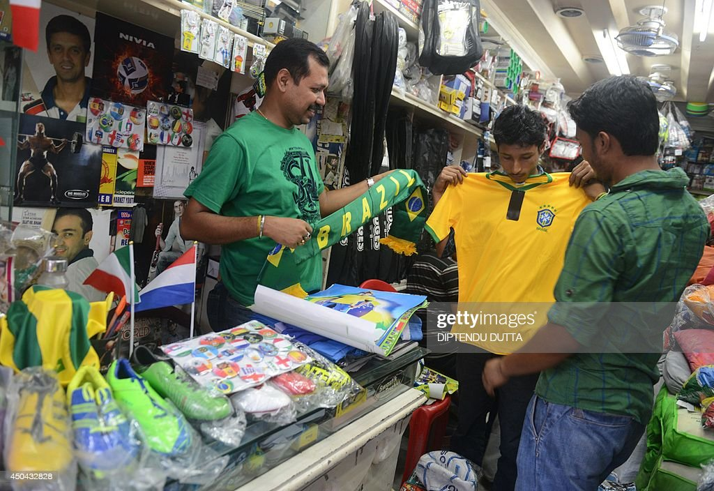 An Indian shopkeeper (L) displays items to youths in search of football memorabilia ahead of the forthcoming FIFA World Cup 2014 in Brazil, at a shop in Siliguri on June 11, 2014. AFP PHOTO/ Diptendu DUTTA