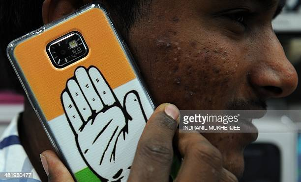 An Indian shopkeeper speaks on his mobile phone adorned with a cover featuring the Indian Congress party symbol in Mumbai on April 2 2014 Snapon...