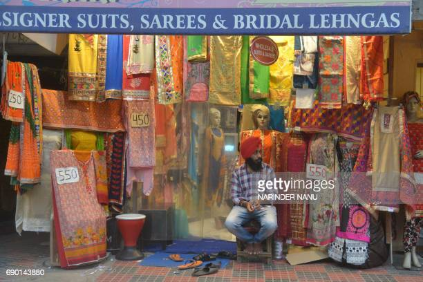 An Indian shopkeeper waits for customers at a shop selling women's suits and wedding outfits in a market in Amritsar on May 30 2017 / AFP PHOTO /...