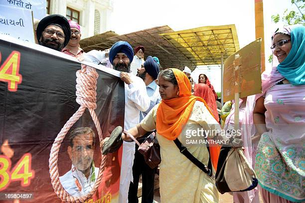 An Indian Sikh beats a poster depicting the image of Congress leader Sajjan Kumar with her shoe during a rally seeking justice for the massacre of...