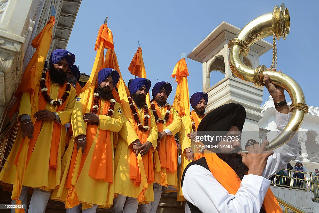 An Indian Sikh devotee blows a horn as 'Punj Pyara' hold Sikh religious flags during a procession at the Golden Temple in Amritsar on January 25, 2013 on the eve of the 331th Birth Anniversary of Sikh warrior, Shaheed Baba Deep Singh. The Gurdwara Shaheed Bunga Baba Deep Singh at the Golden Temple commemorates the memory of Singh and his great deeds.