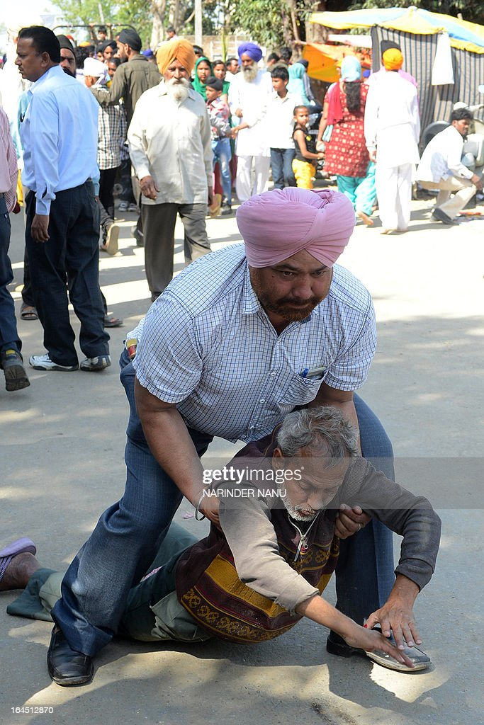 An Indian Sikh devotee helps a drunk man during the religious Babe Rode Shah Mela (Fair) at the 'Samadh' or 'Mazar' (tomb) of Baba Rode Shah in the village of Bhoma Wadala, some 30 kms from Amritsar on March 24, 2013. Thousands of devotees from across the country offer alcohol at the tomb during the two day Babe Rode Shah Mela (Fair) in the northern Indian state of Punjab in the belief their lives will be enhanced in a variety of ways. AFP PHOTO/NARINDER NANU