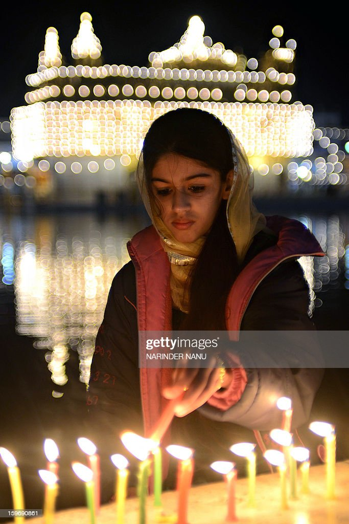 An Indian Sikh devotee lights candles at the Golden Temple in Amritsar on January 18, 2013. Sikhs are celebrating the 348th Birth Anniversary of the tenth Sikh Guru Gobind Singh.