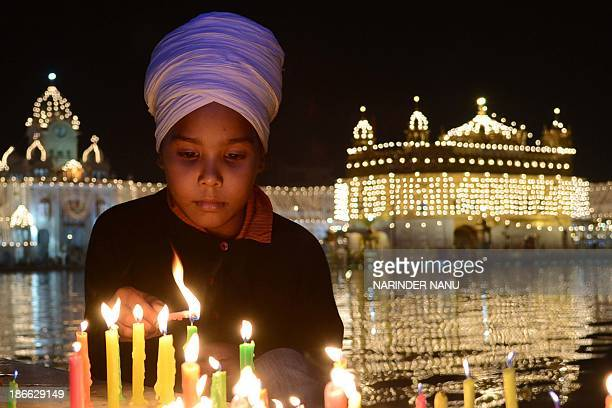 An Indian Sikh devotee lights candles at the illuminated Sikhism's holiest shrine Golden Temple in Amritsar on November 2 on the eve of Bandi Chhor...