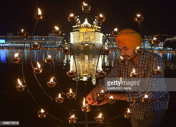 An Indian Sikh devotee lights candles while paying respects at The Golden Temple in Amritsar on November 25 on the occasion of the 546th birth...