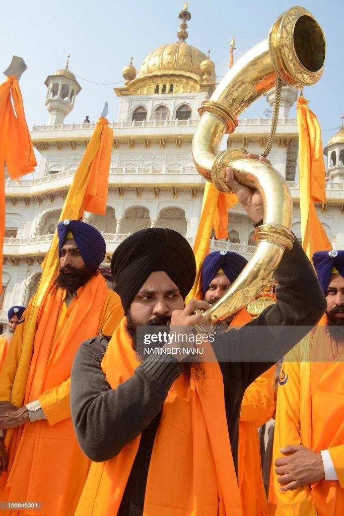 An Indian Sikh devotee plays a musical instrument as he walks with Punj Pyara holding flags of the Sikh religion as they escort a procession from Sri Akal Takhat at The Golden Temple in Amritsar on November 23, 2012, on the eve of the Martyrdom Anniversary of the Ninth Guru of Sikhism, Sri Guru Teg Bahadur. Sri Guru Tegh Bahadur Sahib was born at Amritsar in 1621 and was the youngest son of Sri Guru Hargobind Sahib. He adorned the Sacred Throne of Sri Guru Nanak Sahib from 1664 to 1675.