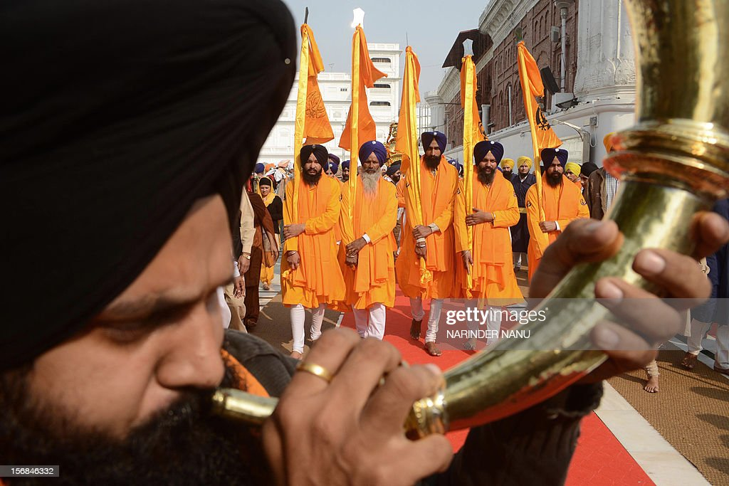 An Indian Sikh devotee plays a musical instrument as he walks with Punj Pyara holding flags of the Sikh religion as they escort a procession from Sri Akal Takhat at The Golden Temple in Amritsar on November 23, 2012, on the eve of the Martyrdom Anniversary of the Ninth Guru of Sikhism, Sri Guru Teg Bahadur. Sri Guru Tegh Bahadur Sahib was born at Amritsar in 1621 and was the youngest son of Sri Guru Hargobind Sahib. He adorned the Sacred Throne of Sri Guru Nanak Sahib from 1664 to 1675. AFP PHOTO/NARINDER NANU