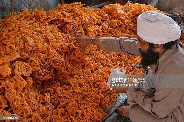 An Indian Sikh devotee puts 'Jalebi' sweets in plastic packets for free distribution to devotees during the Baisakhi festival celebrations held at...