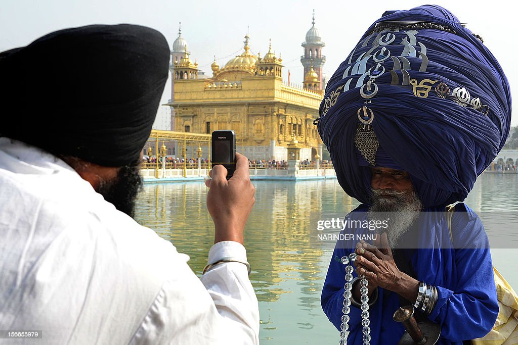 An Indian Sikh devotee takes photographs on his mobile phone of member of the Sikh Nihang Army - traditional Sikh religious warriors - Baba 'Jagir' Singh wearing a turban of some 300 metres in length at the Sikh Shrine, the Golden Temple in Amritsar on November 18, 2012 on the occasion of Martyrdom Day - Jyoti Jot Divas - of Guru Gobind Singh and Sikh warrior, Shaheed Baba Deep Singh. Guru Gobind Singh, who was the Tenth and the last of the living Sikh Gurus, initiated the Sikh Khalsa in 1699, passing the Guruship of the Sikhs to the Eleventh and Eternal Guru of the Sikhs, the Guru Granth Sahib. AFP PHOTO/NARINDER NANU