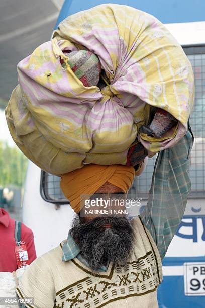 An Indian Sikh evacuated from flooding in Srinagar carries a bundle of items over his head upon arrival at the airport in Amritsar on September 15...