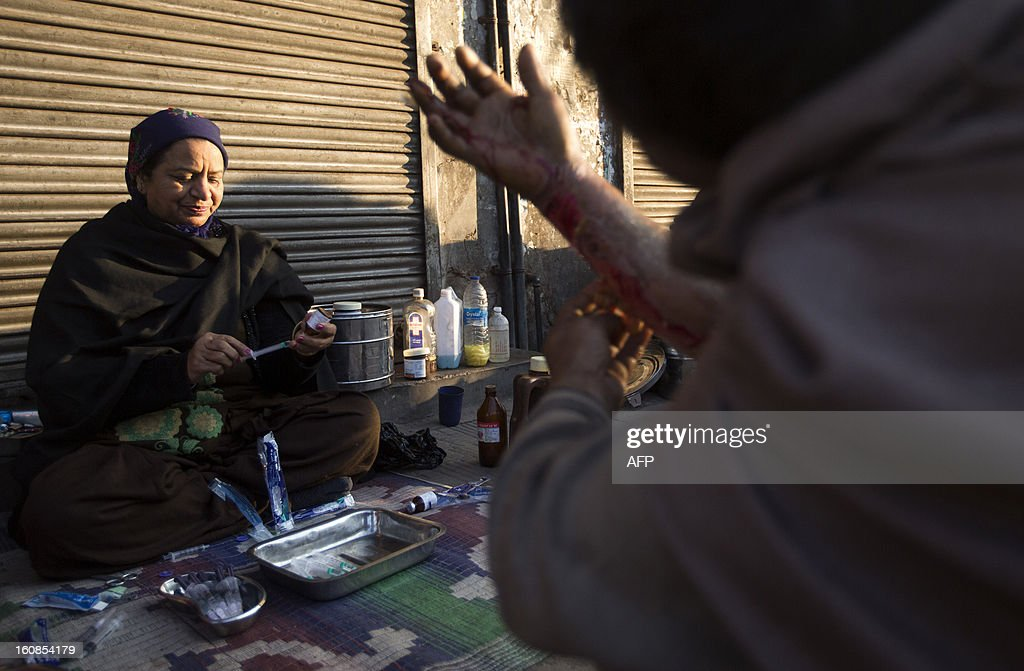 An Indian Sikh medical volunteer prepares a syringe before treating a man with a burned arm in the Old Quarters of New Delhi early on February 7, 2013. Indian medical volunteers have set up roadside clinics in Old Delhi to help treat the homeless, which also includes free medication. The Sikh charity which started the clinic operates it on a daily basis. AFP PHOTO/ Andrew Caballero-Reynolds