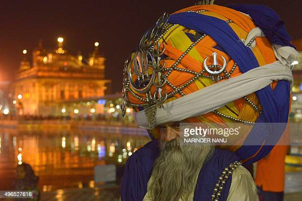 An Indian Sikh Nihang Baba 'Avtar' Singh wears an oversized giant traditional turban as he pay respects at the Golden temple in Amritsar on November...