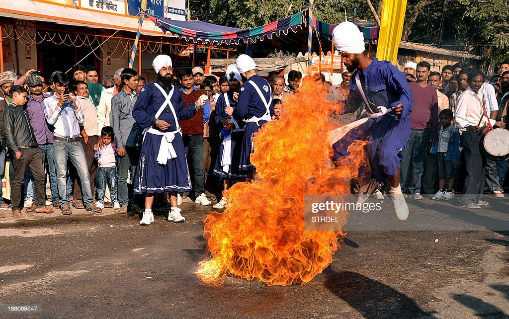 An Indian Sikh Nihang or warrior demonstrates his fire breathing skills as part of the 'Gatka' a traditional martial art during a religious procession in Ranchi on November 15, 2013, ahead of the 544th birth anniversary of Sri Guru Nanak Dev. Guru Nanak was the founder of the religion of Sikhism and the first of ten Sikh Gurus. AFP PHOTO/STR