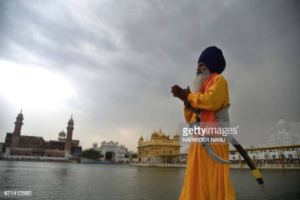 An Indian Sikh 'Nihang' poses as he stands beside The Sarovar of the Sikh shrine The Golden Temple in Amritsar on April 22 2017 / AFP PHOTO /...