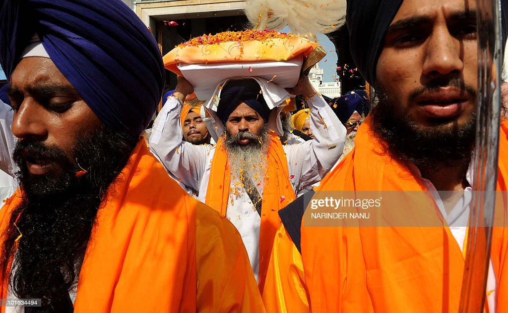 An Indian Sikh priest (C) carries the Guru Granth Sahib (Sikh Holy Book) during 'Fateh Divas' celebrations in Amritsar on June 5, 2010. This year marks the 300 years of the Fateh (victory) of Sirhind and the establishment of the first Khalsa Raaj.