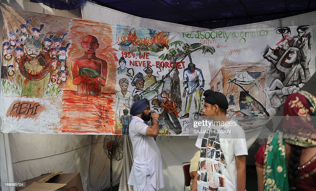 An Indian Sikh stands near a painting depicting the 1984 riots during a demonstration against the acquittal of Congress politician Sajjan Kumar, in New Delhi on May 5, 2013. A court in New Delhi on April 30 acquitted a ruling party politician of murder in a trial linked to the massacre of Sikhs following the 1984 assassination of then Indian prime minister Indira Gandhi.