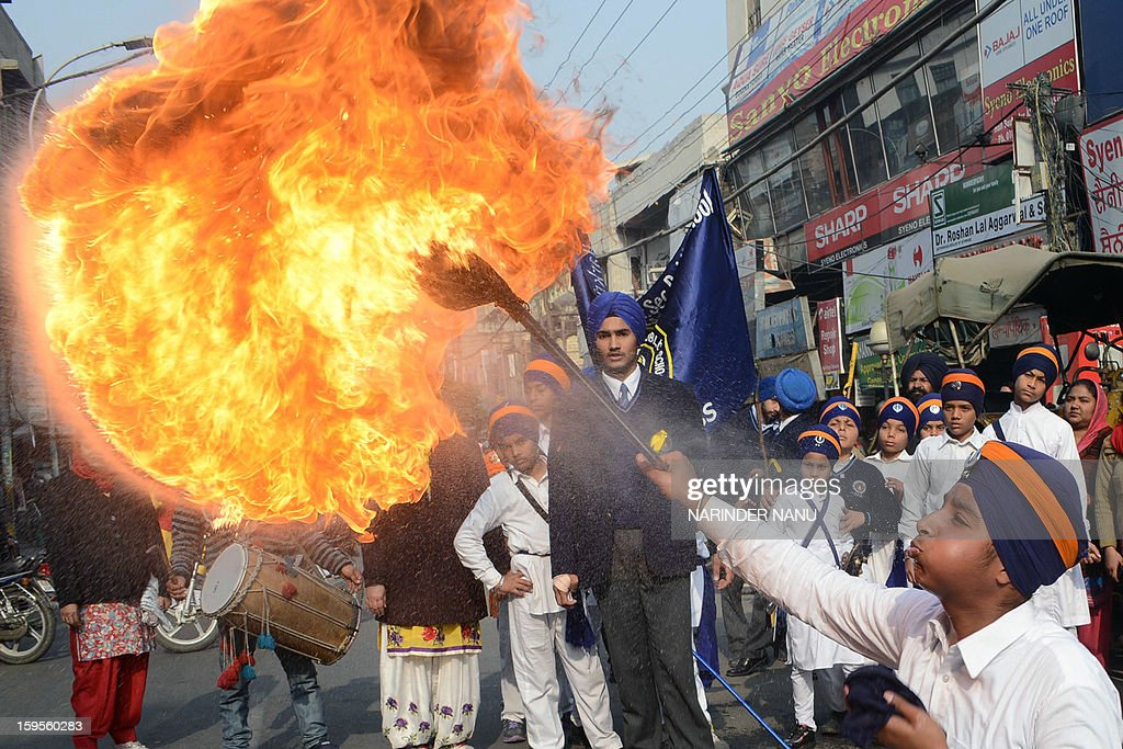 An Indian Sikh youth performs a fire breathing act during a religious procession in Amritsar on January 16, 2013. The procession took place ahead of the 348th Birth Anniversary of tenth Sikh Guru Gobind Singh , which falls on January 18. AFP PHOTO/NARINDER NANU