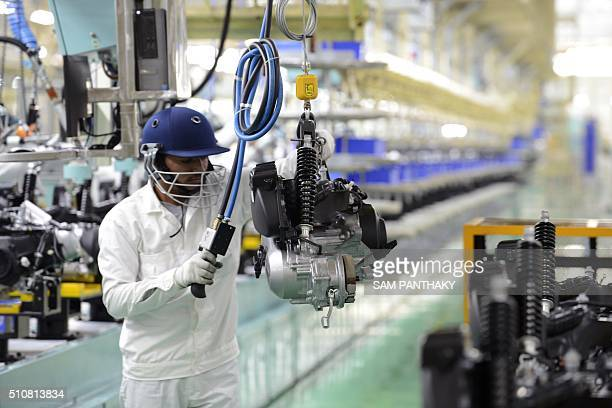 An Indian skilled worker works on an assembly line for Honda Activa scooters at the new plant in Vithalapur some 80 km from Ahmedabad on February 17...