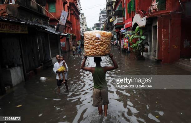 An Indian snack vendor walks along a waterlogged street in Kolkata on June 30 2013 Heavy rains in various parts of Kolkata have disrupted normal life...